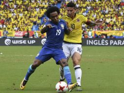 Willian (I), anotador del gol brasileño, disputa un balón con James (D), de Colombia, AFP / L. Acosta