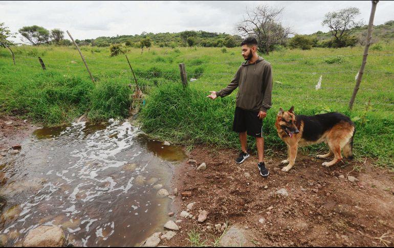Fernando García, junto a su mascota, muestra la contaminación en el arroyo El Popul. La autoridad invita a los afectados a presentar denuncias para poder actuar. EL INFORMADOR/G. Gallo