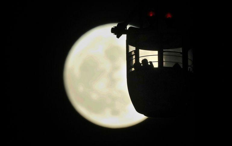 Personas que se pasean en una rueda de la fortuna observan la superluna en Tokio, Japón. El fenómeno se produce cuando la Luna se encuentra en la fase llena y en la distancia más cercana a la Tierra (perigeo).