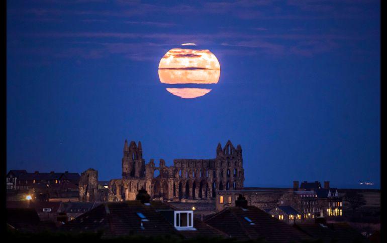 Sobre una abadía en Whitby, Inglaterra. Superluna no es término astronómico oficial, pero en general se refiere a que la Luna llena está 90% o más del perigeo.