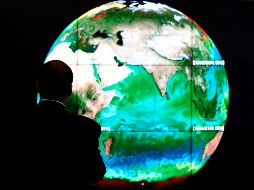 - - (FILES) This file photo taken on November 30, 2015 shows a conference attendee looking at a projection of the Earth  on the opening day of the COP 21 United Nations conference on climate change, on November 30, 2015 in Le Bourget, on the outskirts of the French capital Paris.  Two years after the adoption of a historic global warming pact ahead of the One Planet Summit, sponsored by France, the United Nations and the World Bank, brings together some 4,000 participants and 800 organizations to explore ways to finance climate projects on December 12, 2017. / AFP / ALAIN JOCARD FILES-FRANCE-CLIMATE-WARMING - TO GO WITH AFP STORY BY CATHERINE HOURS