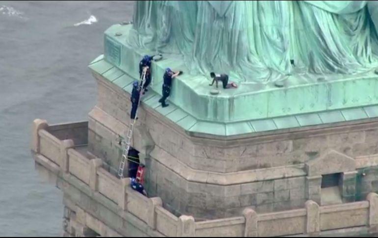 Image result for Mujer intenta escalar la base de la Estatua de la Libertad