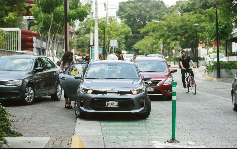 Varios automovilistas se estacionan sobre la ciclovía en López Cotilla, incluso con la tranquilidad para recoger personas, mientras un ciclista tiene que rodear su vía invadida con el riesgo que esto implica. EL INFORMADOR/F. Atilano