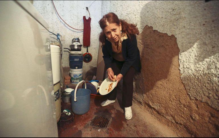 Ante los problemas de abasto y mala calidad de agua que se mantienen en la metrópoli, algunos habitantes como María de la Cruz Silva, de la Colonia División del Norte, en Zapopan, utilizan agua del aljibe para lavar los trastes. EL INFORMADOR / G. Gallo