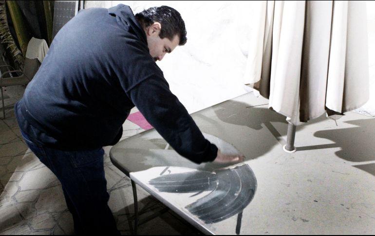 Arturo Ortiz limpia su mesa de jardín que todas las noches se llena de polvo, producto de las ladrilleras que operan en las cercanías de su casa. EL INFORMADOR/A. Camacho