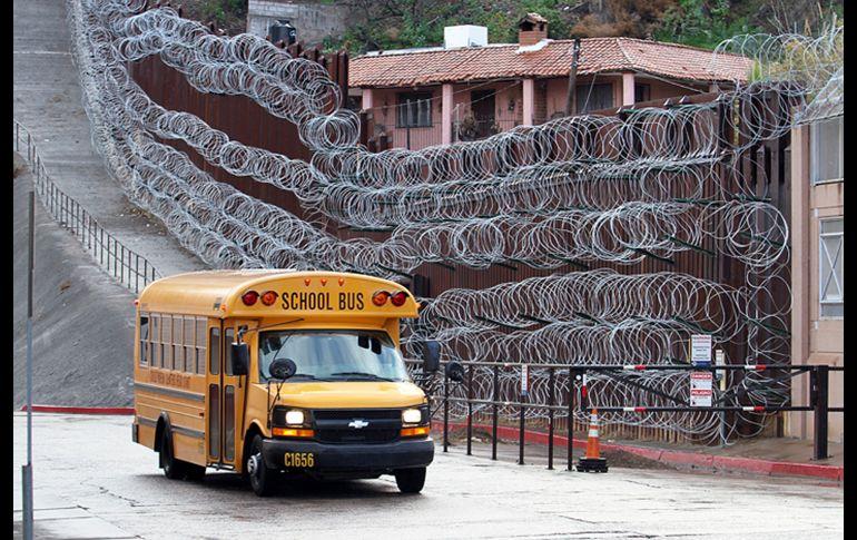 Un autobús escolar pasa junto a la barda reforzada con alambre de púas en el centro de Nogales, Arizona.