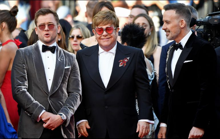 Junto a Elton Jhn le acompañan su esposo David Furnish y al actor Taron Egerton. AFP / C. Simon