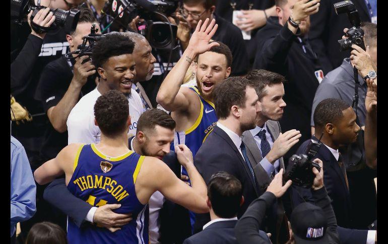 Tras un agónico final, jugadores de los Warriors celebran la victoria. AFP