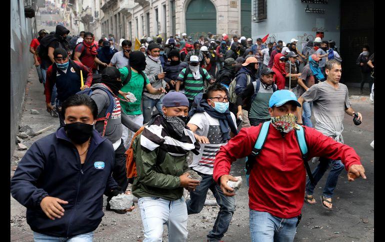 Opositores, algunos con piedras en mano, corren durante enfrentamientos AP/F. Vergara