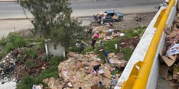 Vuelca tráiler y pobladores roban las pacas de cartón que cargaba