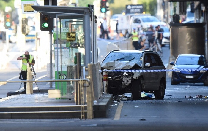 A white SUV (C) sits in the middle of the road as police and emergenc - A white SUV (C) sits in the middle of the road as police and emergency personnel work at the scene of where a car ran over pedestrians in Flinders Street in Melbourne on December 21, 2017. The car ploughed into a crowd in Australia's second-largest city on December 21 in what police said was a